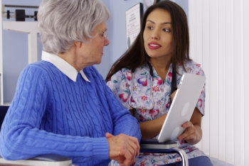 caregiver talking to her patient in wheelchair